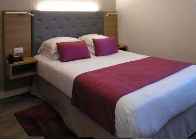 Llit d'hotel amb roba de llit de diferents colors.